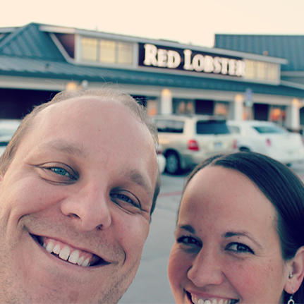 A couple standing in front of a Red Lobster restaurant.