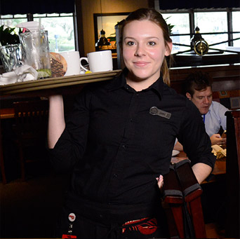 A female server holding a tray of food.