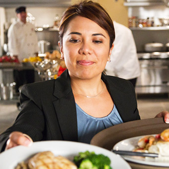 A female manager looking over plates in the kitchen.