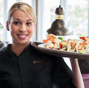 A smiling female server holding a tray of wood-grilled tacos.